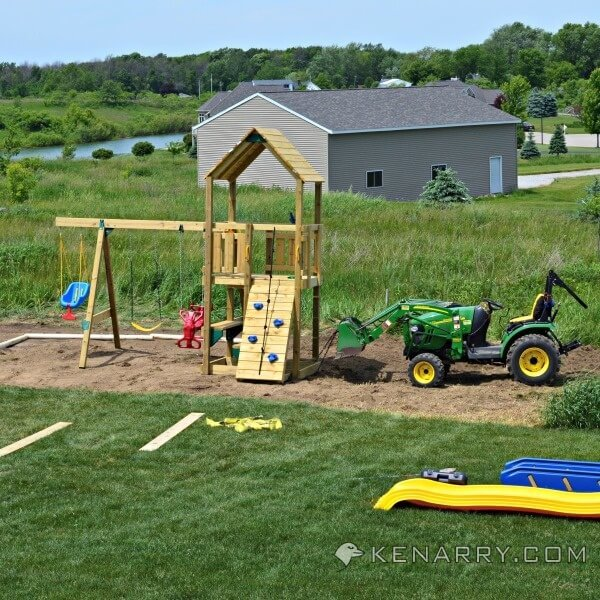 Using a tractor to level the place for a sandbox next to a playset.