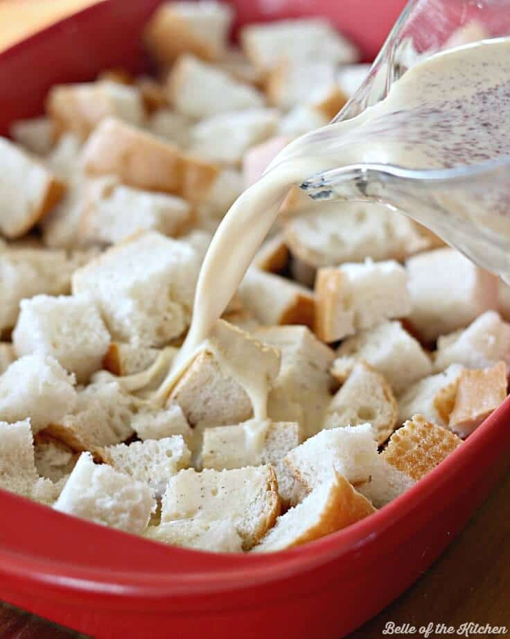 french bread cubes in a baking dish with a french toast milk mixture poured over the top