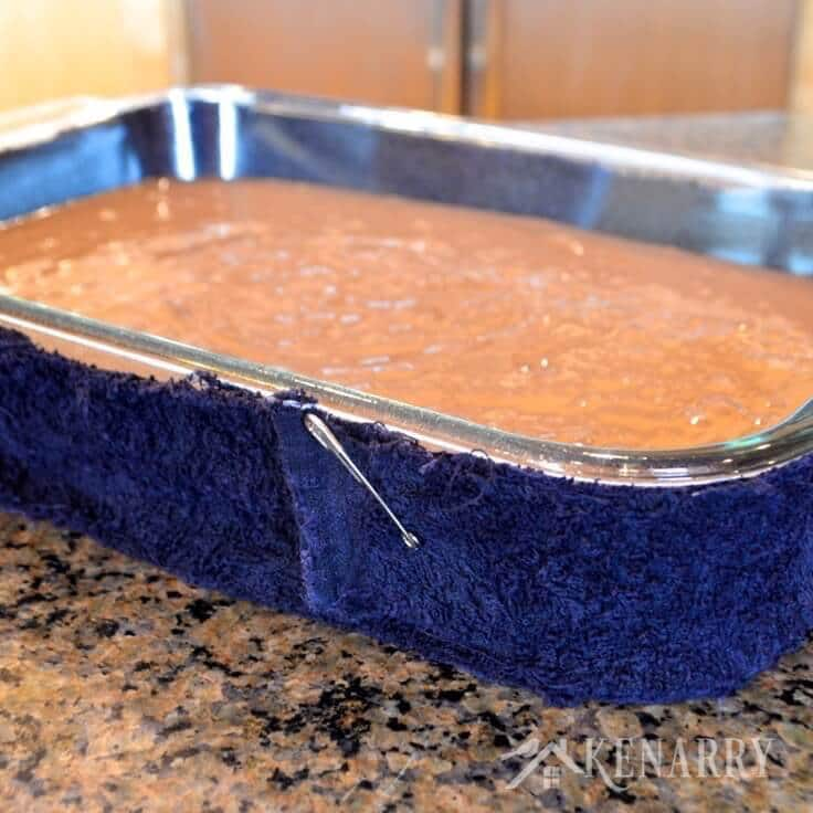 Chocolate cake batter in a baking dish with a blue terrycloth pinned around it to help it bake evenly.