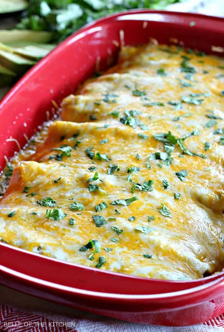 Creamy green chili chicken enchiladas in a red baking dish