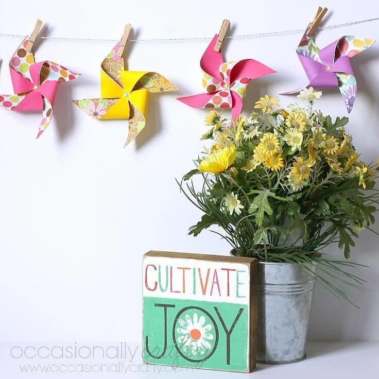 A colorful DIY pinwheel banner hanging up on the wall.