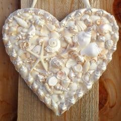 RunningWithSisters.com Make a heart-shaped door hanger with seashells, reals, and rhinestones. Perfect for summer!