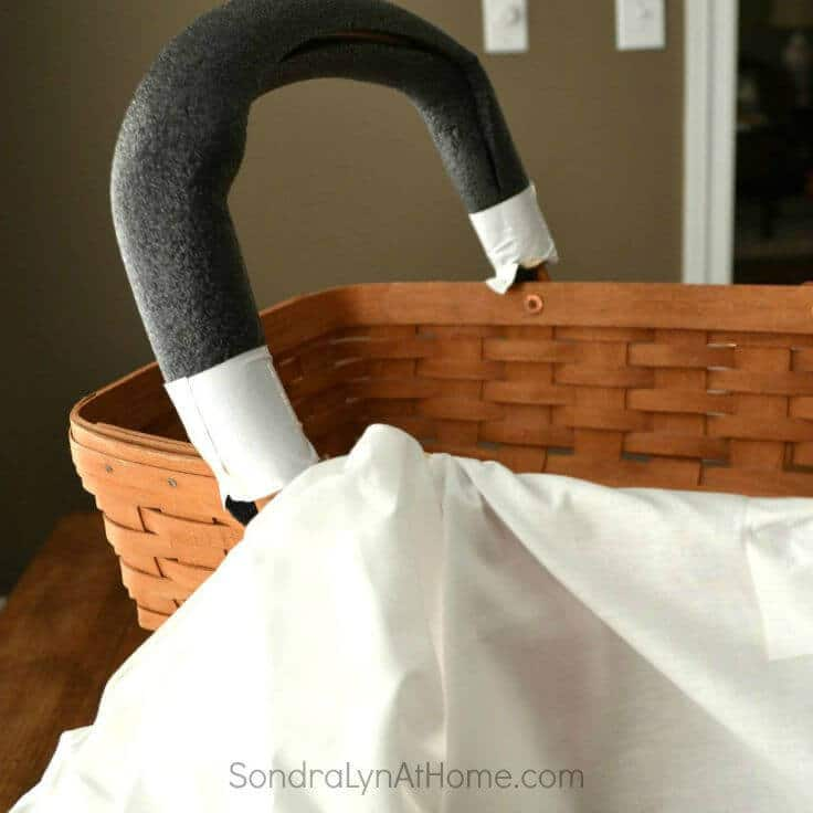 Wrapping a basket's handle with a pool noodle to make a bassinet centerpiece