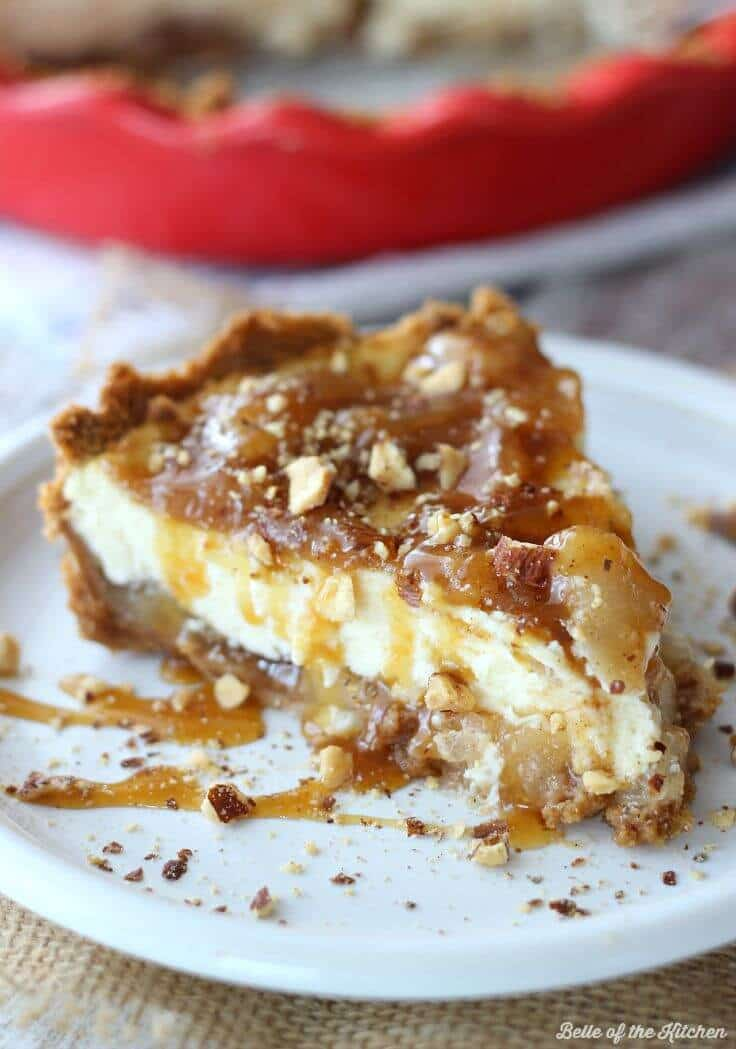 a slice homemade Caramel Apple Cheesecake on a graham cracker crust on a white plate