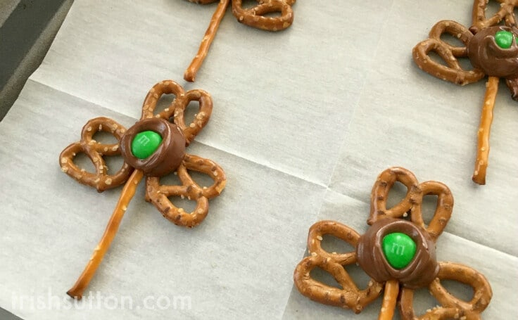 making pretzel shamrocks with Rolos on parchment paper