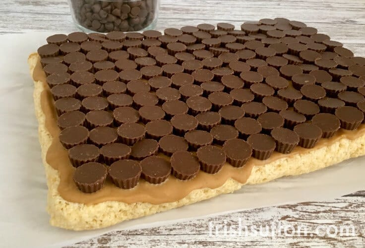 Mini peanut butter cups on top of rice krispie treats.