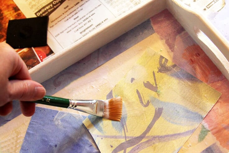 Creating a colorful collage on the bottom of the tray out of scrapbook paper and Mod Podge