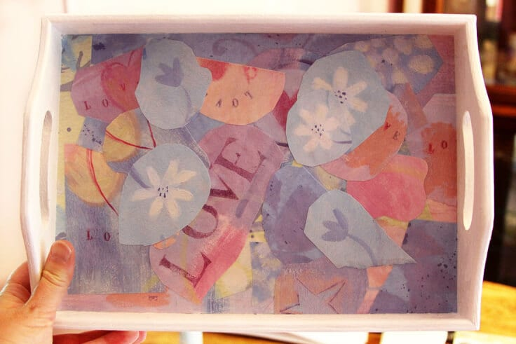 A white wooden tray with colorful pieces of scrapbook paper glued to the inside.