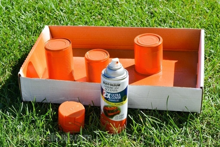 Orange spray paint on empty tin cans.