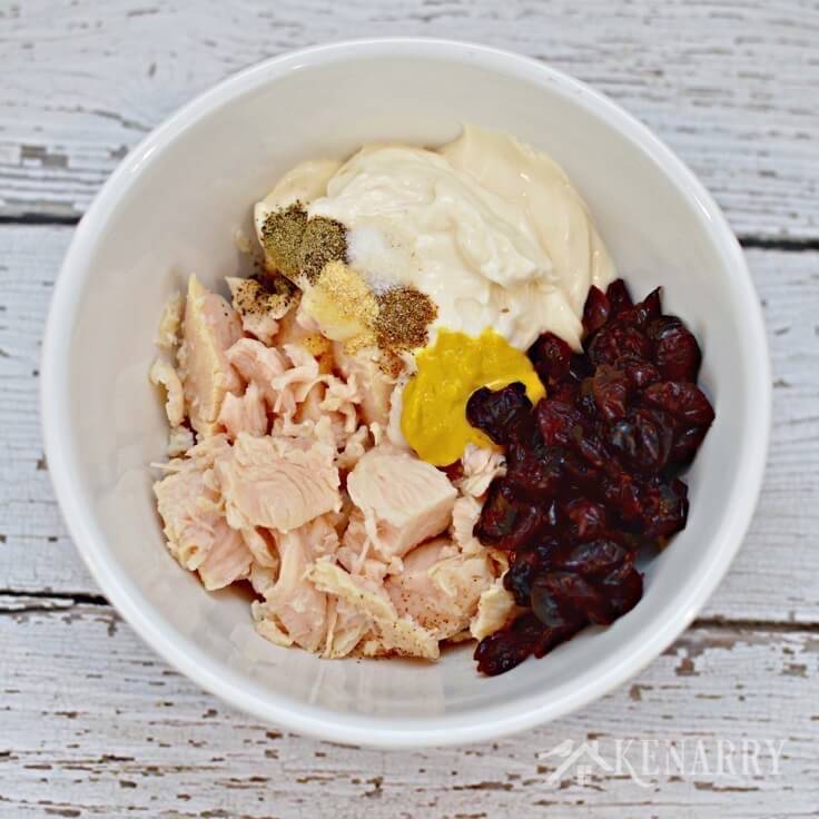A mixing bowl with canned chicken, mayo. cranberries and mustard in it