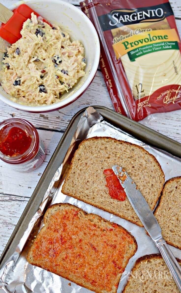 Spreading red pepper jelly on top of wheat bread
