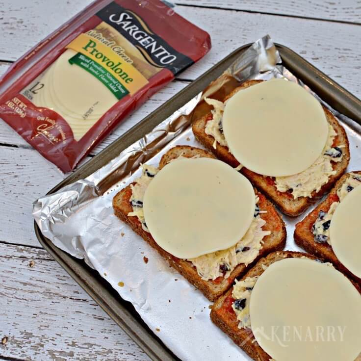 Cheese slices on top of slices of wheat bread with chicken and red pepper jelly