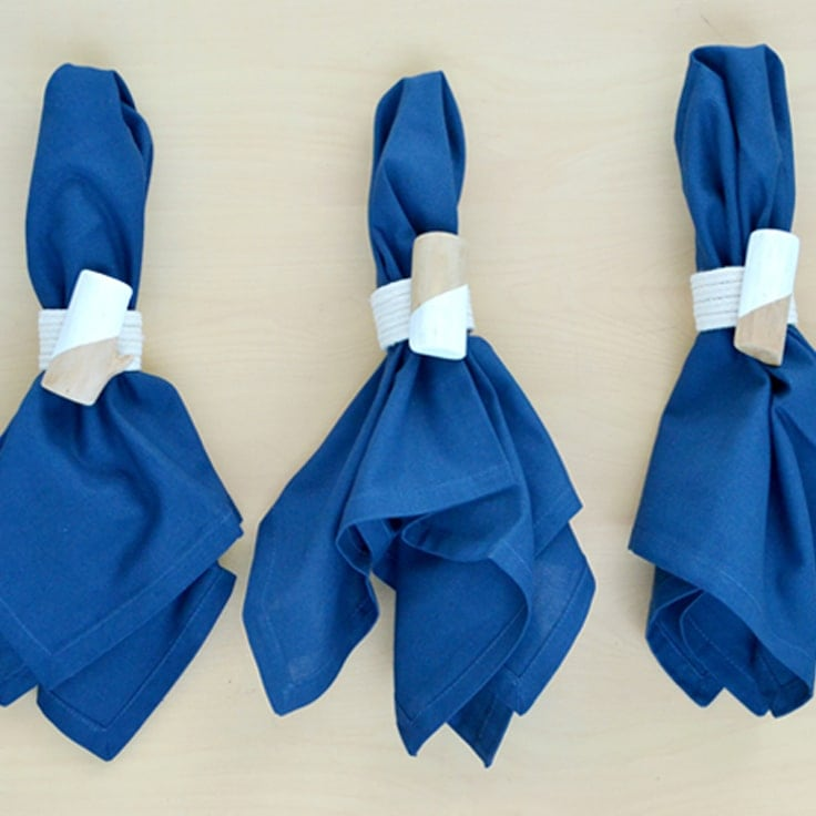 Blue napkins with DIY roped napkin rings around them