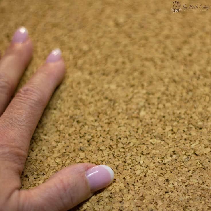 A closeup of a hand on top of a sheet of corkboard
