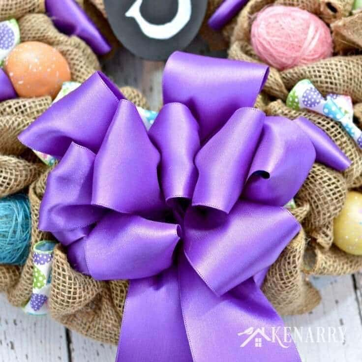 A big loopy purple bow on the burlap wreath