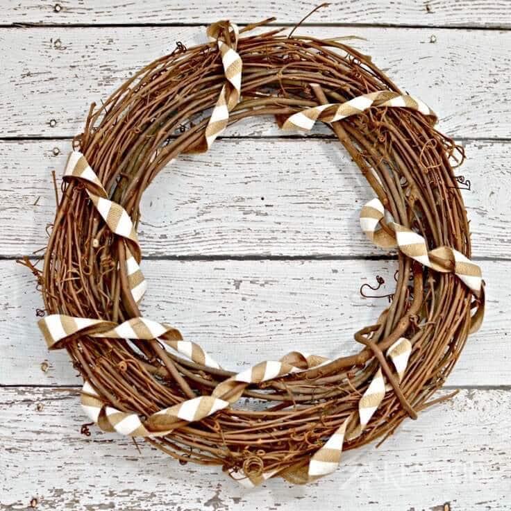 A grapevine wreath with burlap ribbon wrapped around it