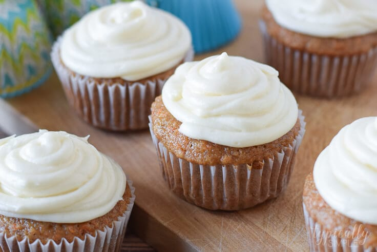 carrot cake cupcakes with cream cheese frosting on a wooden surface