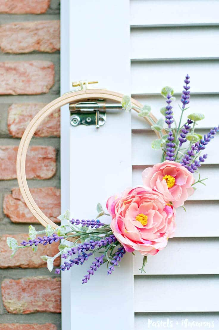 Embroidery hoop spring wreath craft using pink and purple flowers.