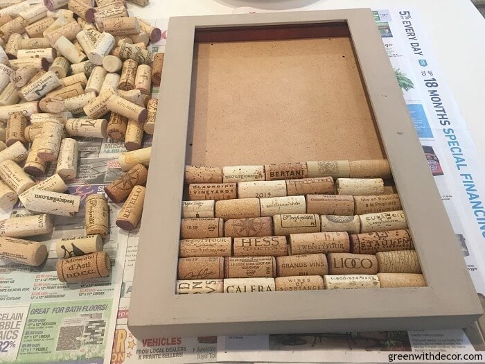 Lining up wine corks inside a shadow box. This will become a bulletin board.