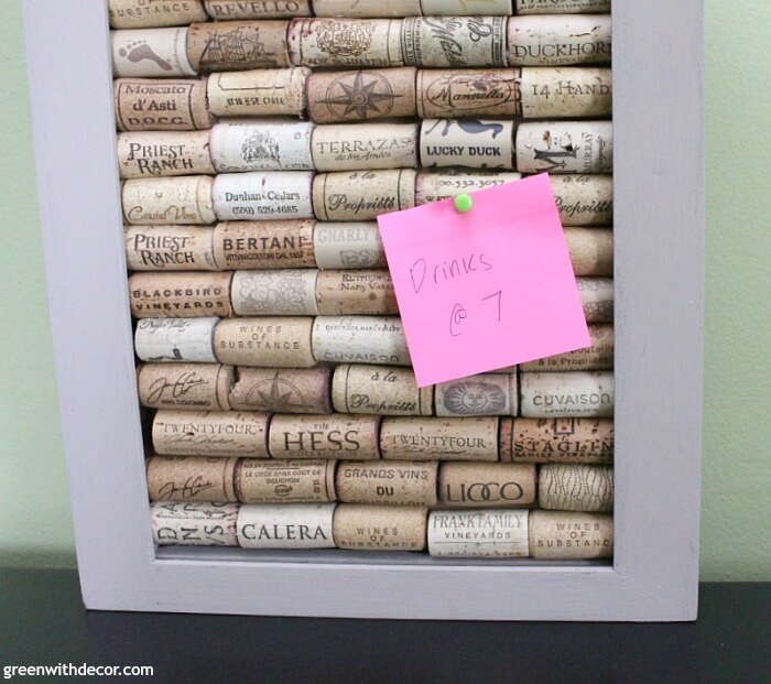 A close up of a pink sticky note pinned to a cork board made out of wine corks.
