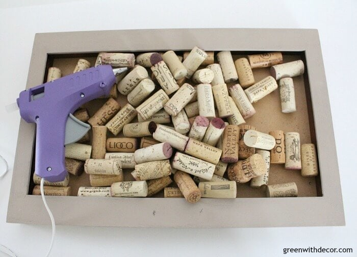 A hot glue gun and loose wine corks in a shadow box.