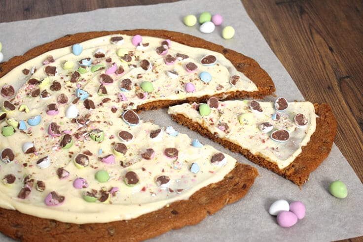 a giant Easter egg cookie pizza on parchment paper