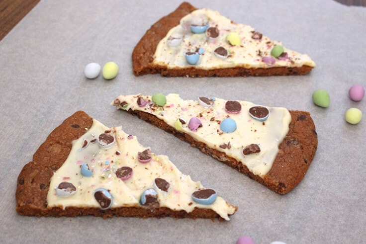 slices of an Easter egg cookie pizza on parchment paper