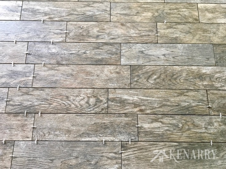 The Marazzi Montagna Rustic Bay 6 in. x 24 in. Glazed Porcelain Floor Tiles used in this cottage update look like weathered wood. This flooring gives the sunroom a rustic farmhouse style look.