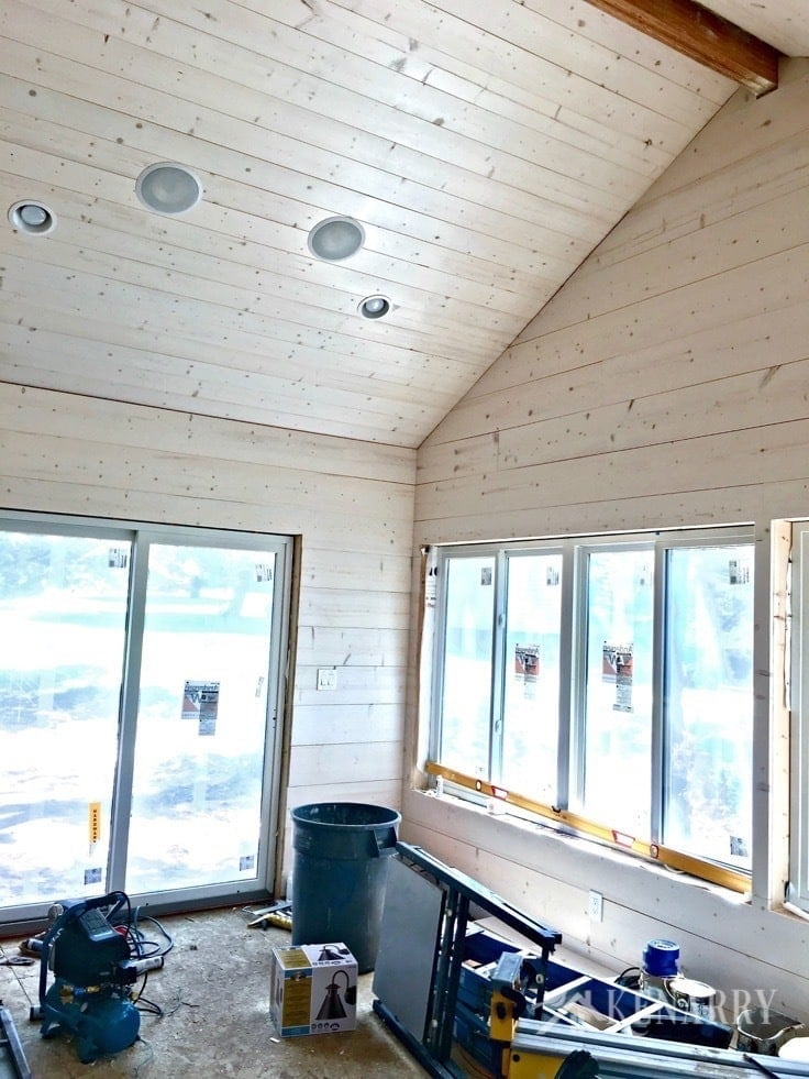 White washed pine plank walls installed in a sunroom as part of a cottage update. These shiplap walls give the room a rustic farmhouse style look.