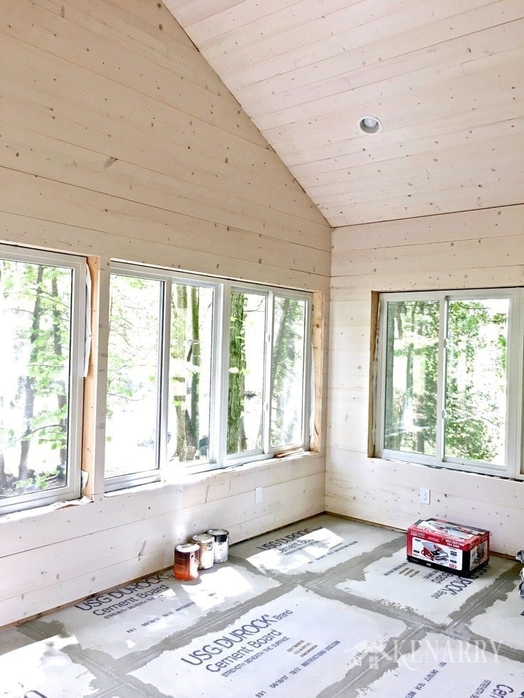 White washed pine plank walls installed in a sunroom as part of a cottage update. These shiplap walls give the room a rustic farmhouse style look. Cement board on the floor prepares the way for porcelain tile that looks like weathered wood.