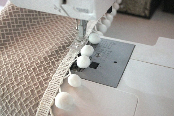 Sewing the pom poms on the valance