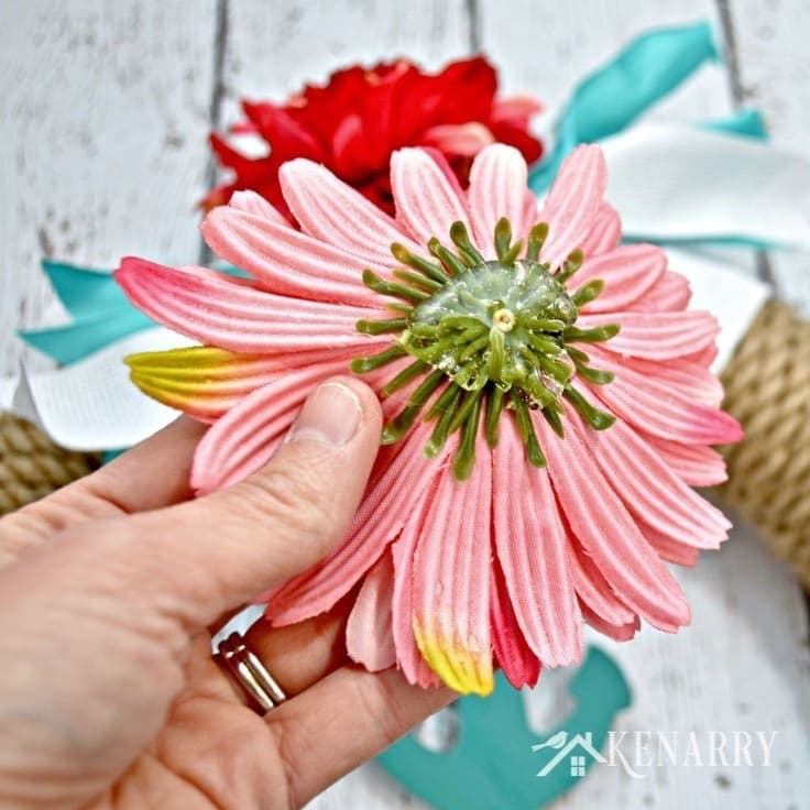 Hot gluing artificial flowers on a wreath