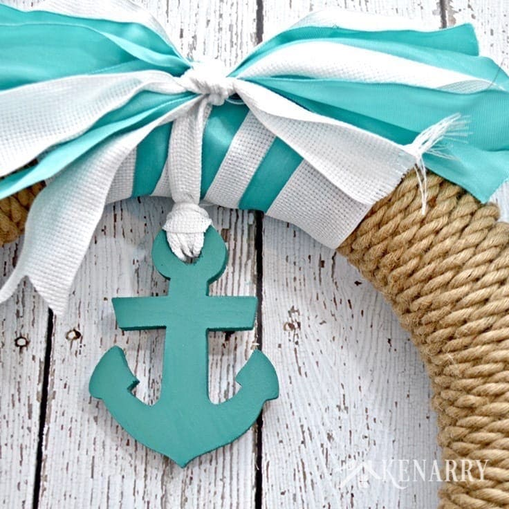 A blue anchor hanging from blue and white ribbon on a nautical wreath