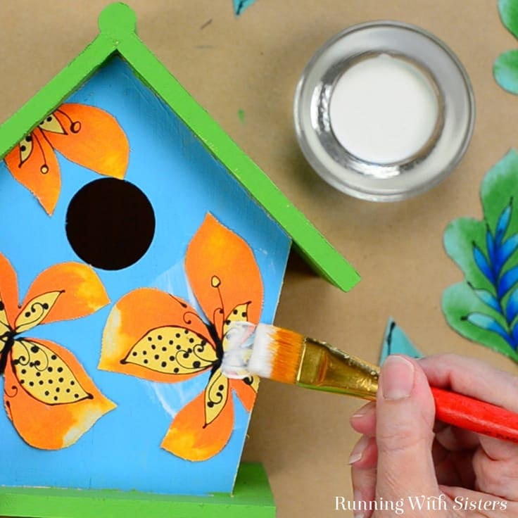Gluing fabric flowers on the birdhouse