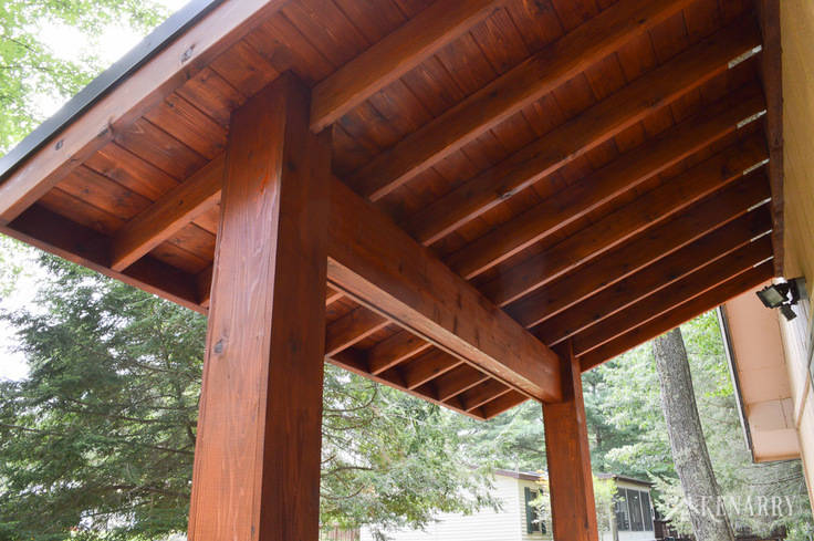 Cedar wood posts and ceiling are perfect for this large craftsman style front porch created for an A-frame cottage home | river rock pillars | outdoor patio | home idea