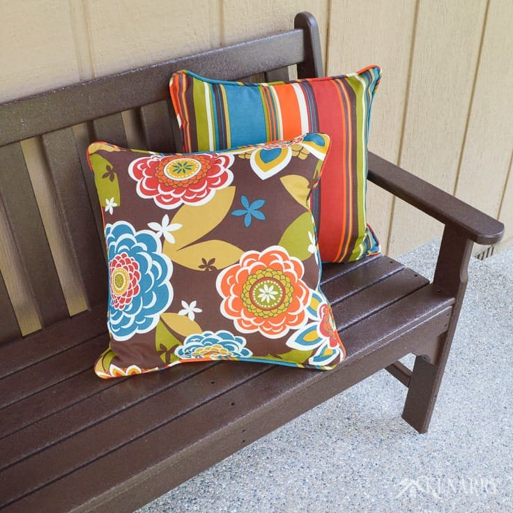 Bright colorful indoor/outdoor pillows dress up a brown polywood mission style bench on a new craftsman style front porch built on the front of an A-frame cottage home | home idea | outdoor patio | outdoor living | polywood bench