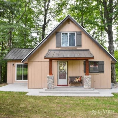 Add craftsman style to an a-frame cottage by adding a front porch with a metal roof, cedar posts, river rock pillars and a mission style bench | home idea | exposed aggregate concrete | a-frame house | outdoors