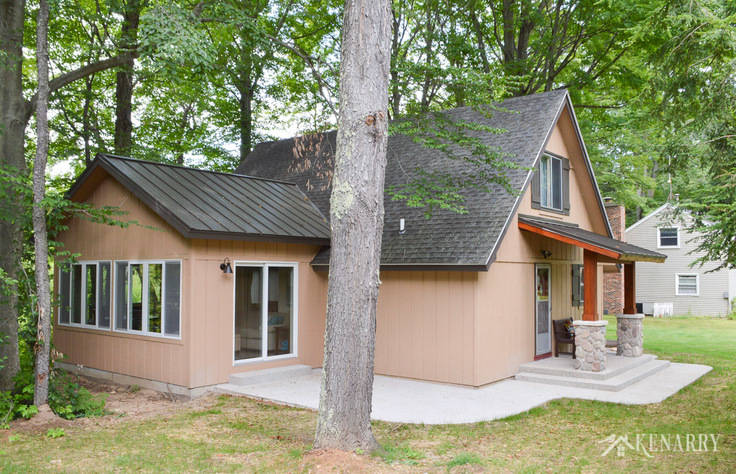 A sunroom and front porch were added to this a-frame cottage on a wilderness river to give the home a beautiful craftsman style look | river rock pillars | exposed aggregate concrete | home idea | stained cedar wood | concrete patio