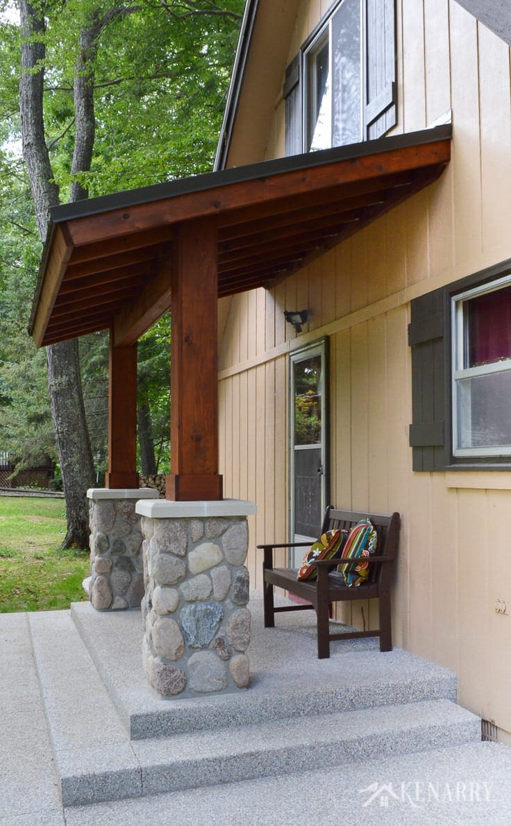 River rock pillars and cedar wood are used to create a craftsman style porch for an A-frame cottage home on a wilderness river | home idea | outdoor patio | mission style bench | exposed aggregate concrete