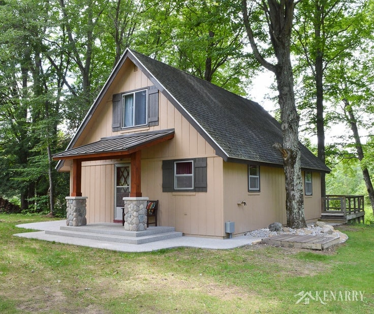 A-frame cottage gets a whole new look with board and batten shutters and a craftsman style porch surrounded by an exposed aggregate patio. river rock pillars | home idea | cedar posts | sloped metal roof