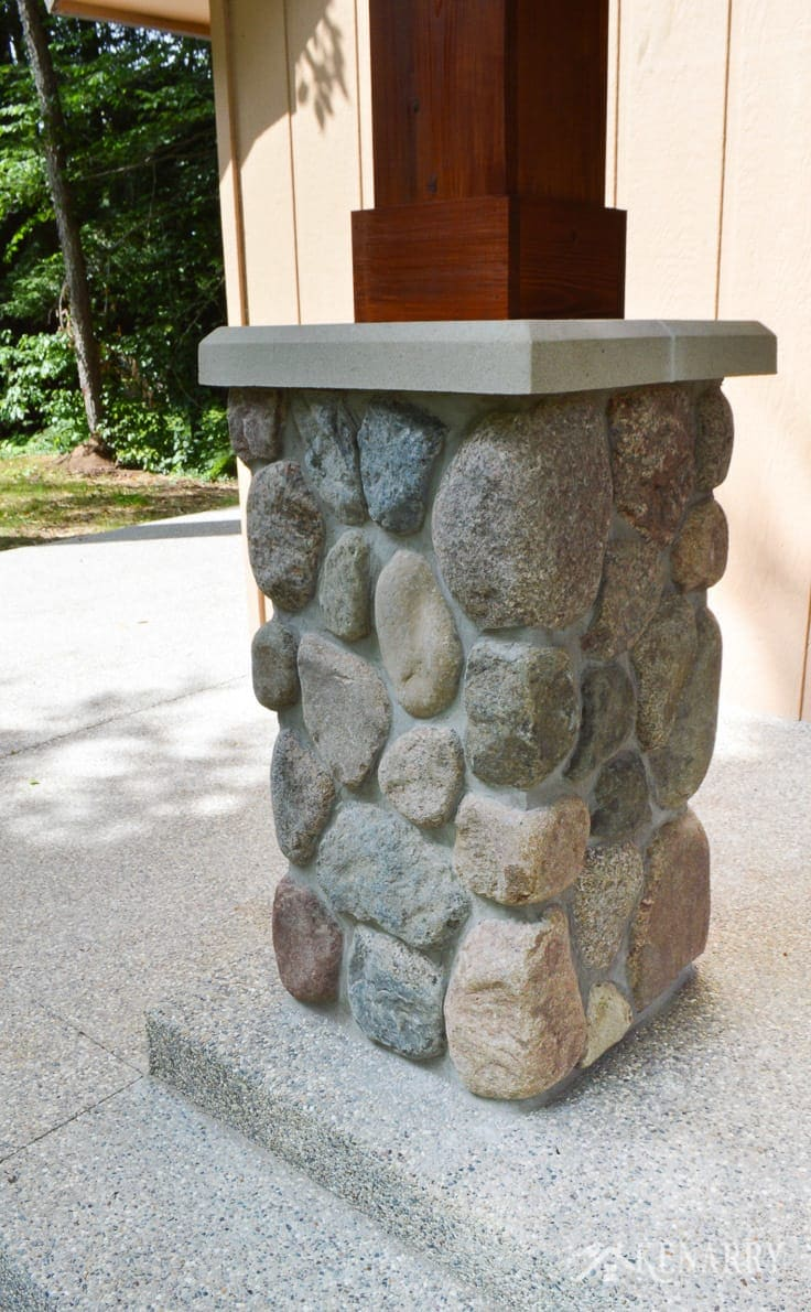 River rock pillars hold up cedar posts for this craftsman style porch on the front of an a-frame cottage | home idea | stone pillar | exposed aggregate concrete