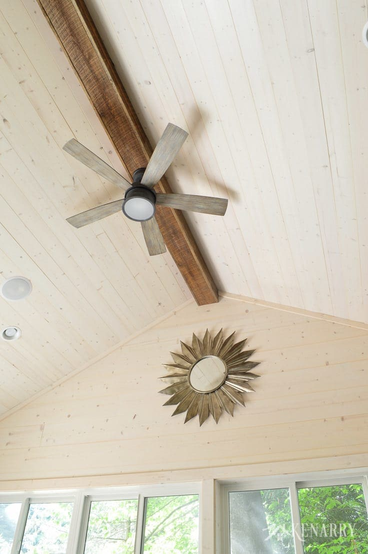 Exposed wood beam with a ceiling fan and a large metal sunburst mirror adds industrial style to this cottage home with vaulted shiplap ceiling and walls | sunroom | shiplap walls | plank wall | whitewashed pine wood walls | home decor | home ideas | farmhouse style