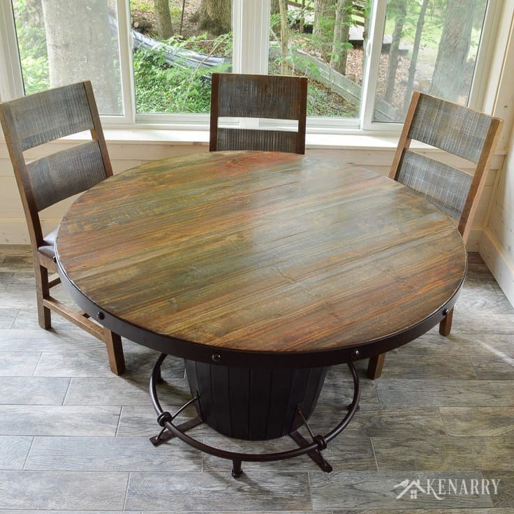 This round dining table with a barrel base and distressed chairs adds industrial style to a cottage sunroom - the antique multicolor round dining set from International Furniture Direct | dining room | shiplap walls | plank wall | whitewashed pine wood walls | porcelain tile floor | wood tile flooring | home decor | furniture | home ideas | farmhouse style