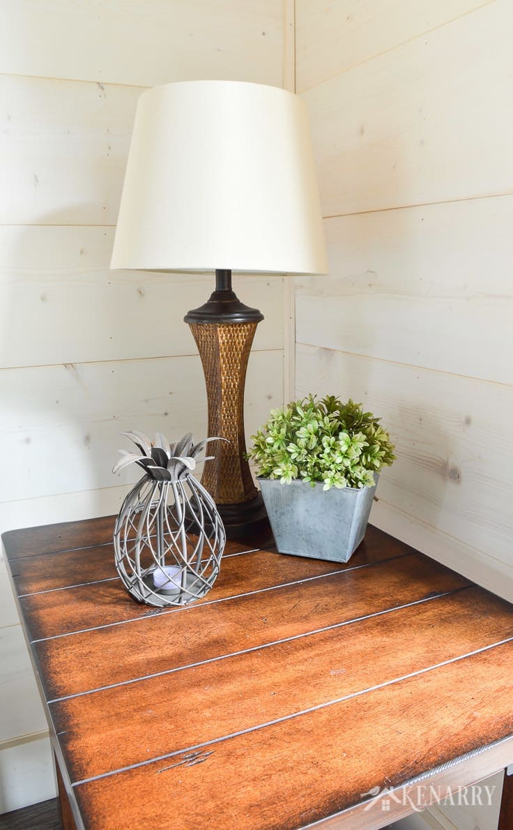 A rattan lamp and pineapple tealight candleholder and plant on a distressed industrial style side table add coastal style in a cottage sunroom with shiplap walls | sunroom | shiplap walls | plank wall | whitewashed pine wood walls | furniture | home decor | home ideas | farmhouse style