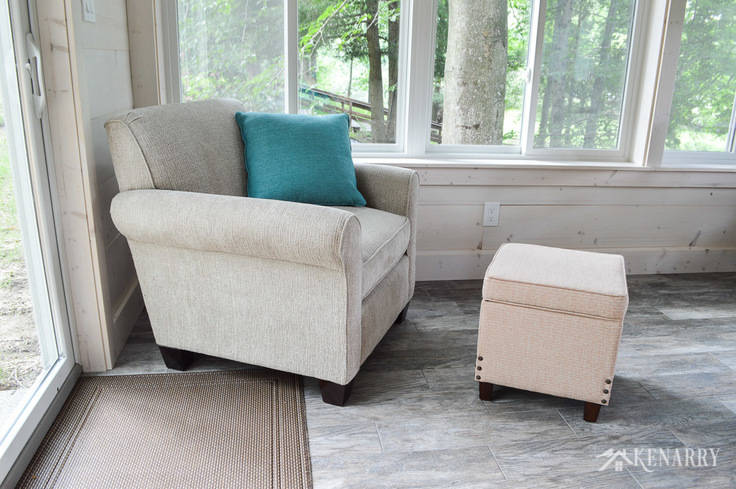 Angie Chair (#4634) from England Furniture in the color Perth Sand with a storage ottoman | cottage sunroom | footstool | hinged ottoman with storage | shiplap walls | plank wall | whitewashed pine wood walls | porcelain tile floor | wood tile flooring | home decor | furniture | home ideas | farmhouse style