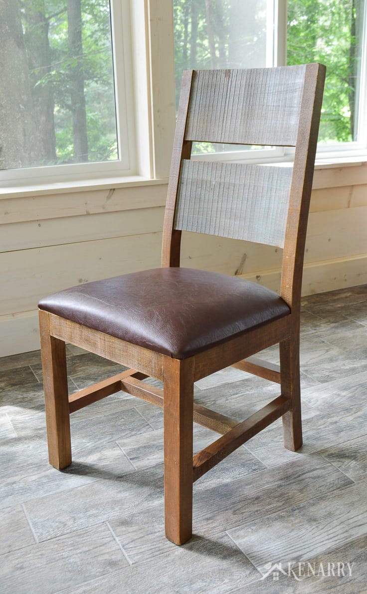 Distressed dining chair in a cottage sunroom - part of the antique multicolor round dining set from International Furniture Direct | dining room | shiplap walls | porcelain tile floor | wood tile flooring