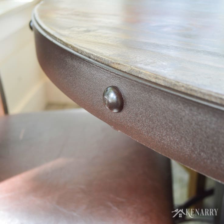 The iron edge of this round dining table adds industrial style to a cottage sunroom - the table is part of the antique multicolor round dining set from International Furniture Direct | dining room | farmhouse style