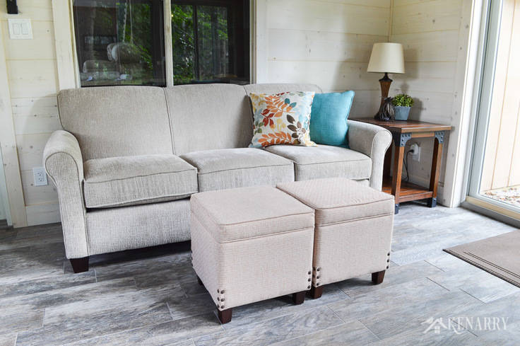Put two together two upholstered footstools or ottomans to create a coffee table in a cottage sunroom | Angie Sofa (#4635) from England Furniture in the color Perth Sand | rattan lamp with side table | shiplap walls | plank wall | whitewashed pine wood walls | porcelain tile floor | wood tile flooring | home decor | furniture | home ideas | farmhouse style
