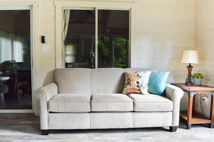 Angie Sofa (#4635) from England Furniture in the color Perth Sand in a cottage sunroom | rattan lamp with side table | shiplap walls | plank wall | whitewashed pine wood walls | porcelain tile floor | wood tile flooring | home decor | furniture | home ideas | farmhouse style