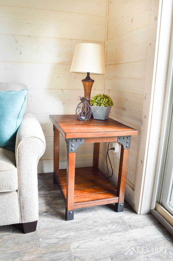 A distressed industrial style side table with a rattan lamp gives farmhouse style to a cottage sunroom with shiplap walls | plank wall | whitewashed pine wood walls | furniture | home decor | home ideas